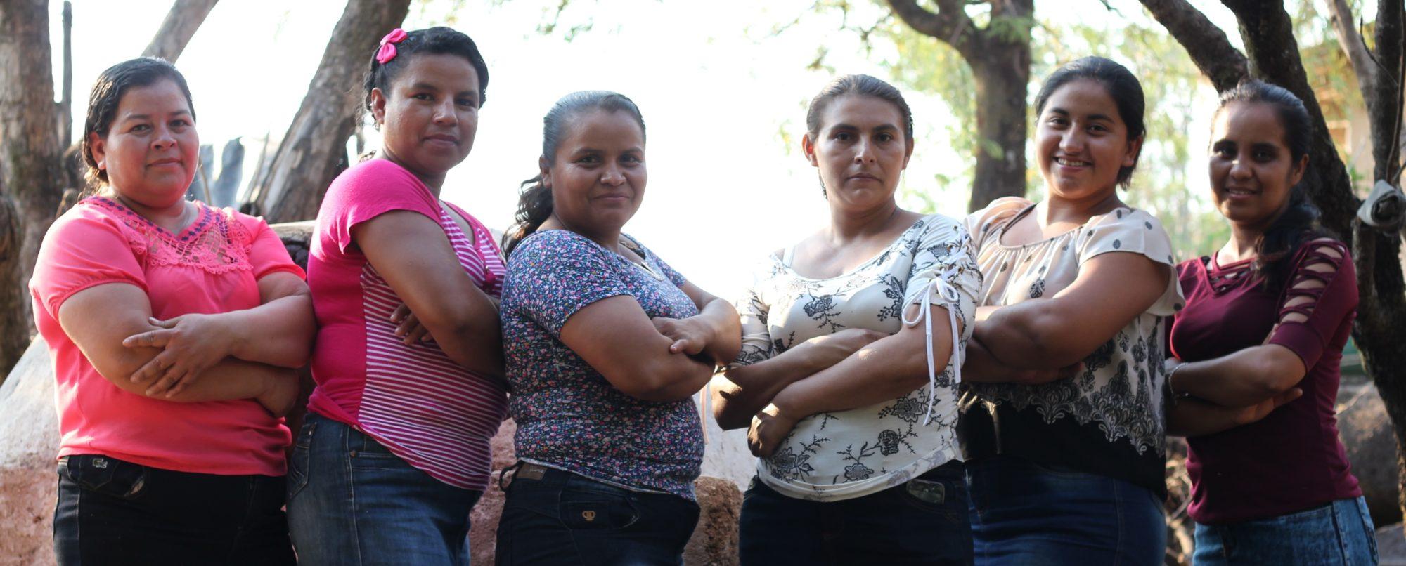 Seis mujeres paradas con brazos cruzados mirando a la cámara