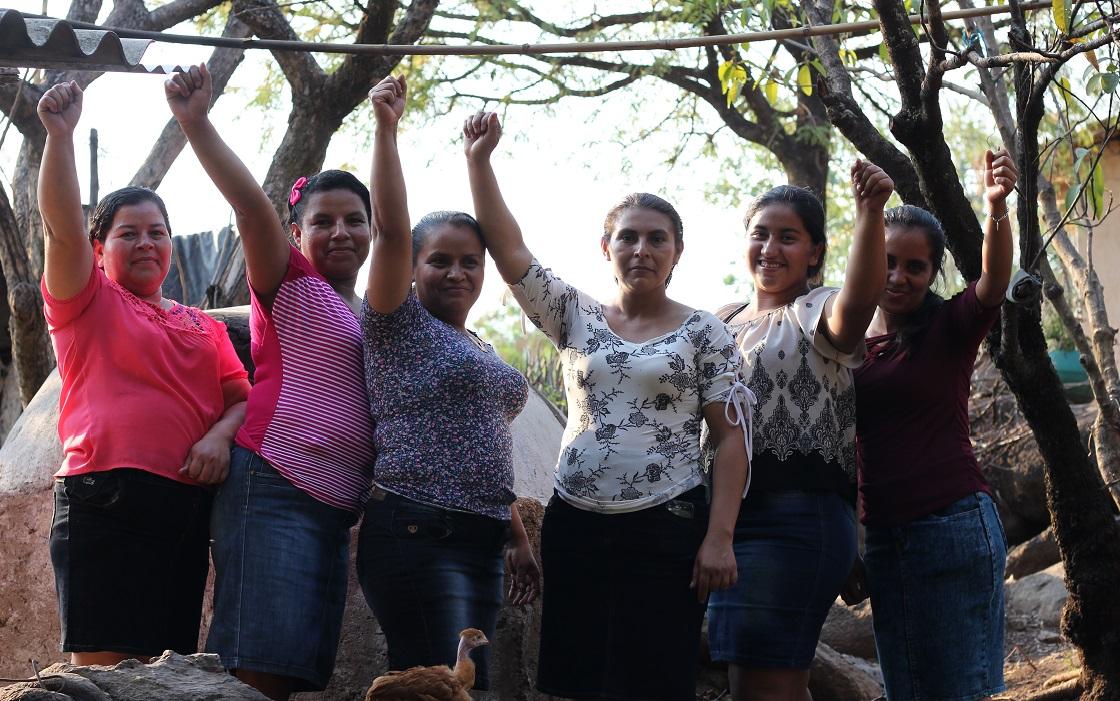 Seis mujeres con los puños arriba mirando a la cámara